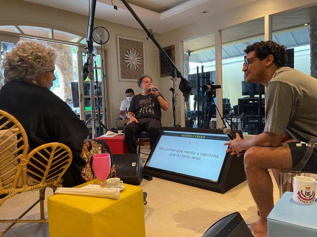 Alcione (esq.) durante ensaio em sua casa no Rio ao lado de Criolo para live da Mastercard; ao fundo, o produtor Zé Ricardo (Rachel Xavier - 21.mai.2021/Divulgação)